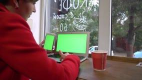 девушка дела в coffeshop, работающ используя компьтер-книжку и телефон сток-видео