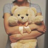 Девушка держащ и обнимающ плюшевый медвежонка Идея концепции - до свидания к детству сбор винограда типа лилии иллюстрации красны Стоковые Фото