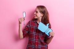 Девушка, держа бумажную зубную щетку и знак обратной связи, усмехаясь и смотря щетку стоковое изображение