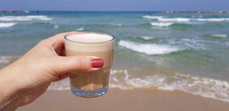 Девушка держа в ее кофе latte руки в прозрачном стекле против морских вод стоковые фотографии rf