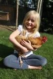 Девушка держа ее цыпленка курицы любимчика сидя в лета садовничает Стоковое Изображение RF