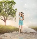 Девушка держа ее щенка на волшебном ручейке Стоковые Изображения