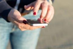 Девушка держа мобильный телефон в руках стоковая фотография rf