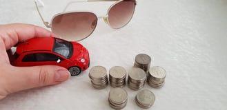Девушка держа небольшую красную игрушку abarth Фиат 500 на белой таблице около солнечных очков и кучи израильтянина монетки одног стоковое изображение rf