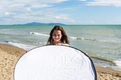 Девушка держа рефлектор фото на пляже Стоковое Изображение
