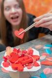 Девушка держа сердце с палочками стоковое изображение