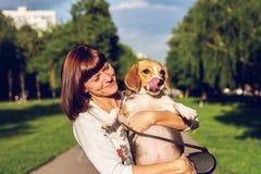 Девушка держа собаку в ее оружиях на предпосылке природы на лете Фото образа жизни стоковые фотографии rf