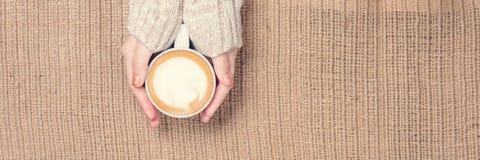 Девушка держа чашку кофе с искусством latte концепция времени leasure Стоковые Изображения