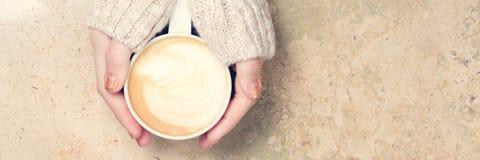 Девушка держа чашку кофе с искусством latte концепция времени leasure Стоковые Фотографии RF