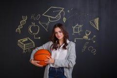 Девушка держа шарик корзины, стоя около доски с знаками науки и знания стоковое фото