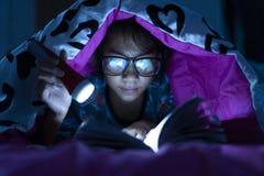 Девушка держа электрофонарь пока одеяло книг чтения стекел носки в комнате кровати стоковое изображение