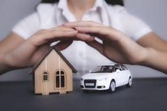 Девушка держит дом и автомобиль стоковые фотографии rf