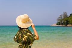 Девушка держит ее шляпу и смотрит океан Стоковые Фотографии RF