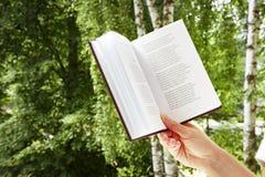 Девушка держит книгу в конце-вверх природы Рука ` s женщины с книгой Хобби для того чтобы прочитать книгу Стоковая Фотография