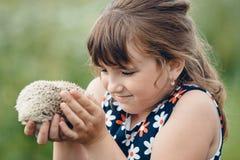 Девушка держит колючего ежа на его руках стоковое фото rf