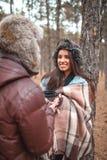 Девушка держит кружку с чаем и смотрит на парня Outdoors в холодном лесе осени Стоковые Изображения RF