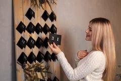 Девушка держит лист календаря 31th -го декабрь ` S Eve Нового Года стоковое фото