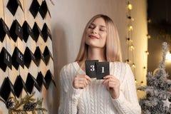 Девушка держит лист календаря 31th -го декабрь ` S Eve Нового Года стоковая фотография rf