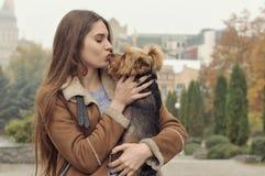 Девушка держит малую собаку в ее оружиях, объятиях и целует ее Стоковая Фотография RF