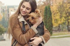 Девушка держит малую собаку в ее оружиях, объятиях и целует ее Стоковое Изображение RF