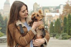 Девушка держит малую собаку в ее оружиях, объятиях и целует ее Стоковое Фото