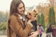 Девушка держит малую собаку в ее оружиях, объятиях и целует ее Стоковое Изображение