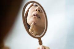 Девушка держит небольшое зеркало перед ей и рассматривает кожу на ее стороне с угорь Забота для кожи проблемы стоковое изображение rf