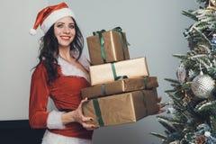 Девушка держит 4 подарка в оболочке золота в квартире украшенной на Новый Год Молодая женщина в красных тягах костюма Санта Клаус стоковая фотография rf