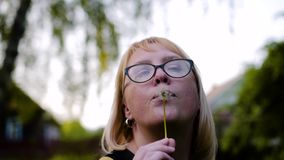 Девушка держит цветок одуванчика перед ее и дуновения с белых семян Они красиво разбросаны к сторонам o акции видеоматериалы