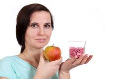Девушка держит яблоко и витамины в руке Стоковая Фотография