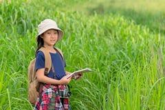 Девушка детей азиатская держа карты и рюкзаки перемещения идя в зеленый лес стоковое фото