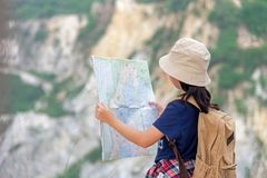 Девушка детей азиатская держа карты и рюкзаки перемещения магнитного компаса стоя в горе для природы образования стоковые фотографии rf