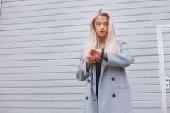 Девушка детенышей модно одетая белокурая в пальто использует умный браслет стоя outdoors стоковая фотография
