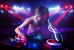 Девушка диск-жокея играя музыку с светлыми фокусировками коротких волн на этапе Стоковые Изображения