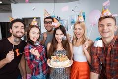 Девушка дня рождения держит торт с свечами Девушки и парни стоят вокруг ее Стоковое Фото