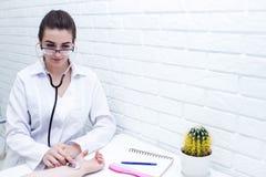 Девушка доктора слушает к ИМПу ульс на терпеливой руке ` s стоковая фотография