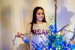 Девушка дома пока украшающ рождественскую елку Стоковые Изображения RF