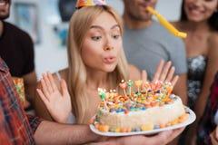 Девушка дует вне свечи на именнином пироге Девушка дует вне свечи и делает желание Стоковое фото RF