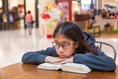 Девушка думая о рассказе книги она читает на таблице Стоковое фото RF