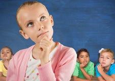Девушка думая перед друзьями и голубой стеной стоковые фото