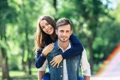 Девушка едет дальше назад парня, усмехающся на камере outdoors Стоковое Изображение