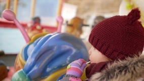 Девушка едет на carousel и лижет конфету видеоматериал