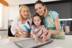 Девушка, ее мать и бабушка варят домодельные печенья Круги распространения матери и девушки теста на листе выпечки Стоковая Фотография RF