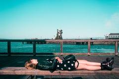 Девушка лежа вниз на стенде на Сан-Франциско, Калифорнии стоковое изображение rf