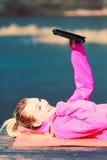 Девушка лежа в парке используя таблетку Стоковые Изображения RF