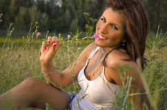 Девушка лежа в цветке травы пахнуть Стоковое Изображение RF