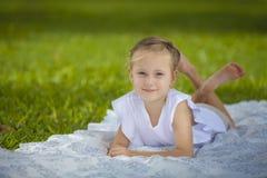 Девушка ся на белом одеяле стоковые изображения