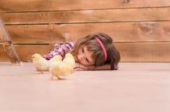 Девушка лежа на поле и наблюдая для цыплят Стоковые Фото