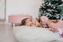 Девушка лежа на подушке рядом с рождественской елкой Стоковое фото RF