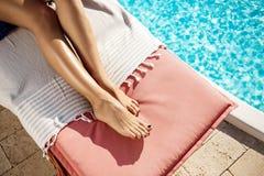 Девушка лежа на фаэтоне около бассейна Закройте вверх ног Стоковое фото RF